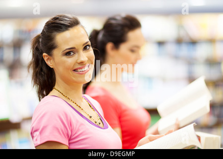 two female university students reading books in library or bookstore - Stock Photo