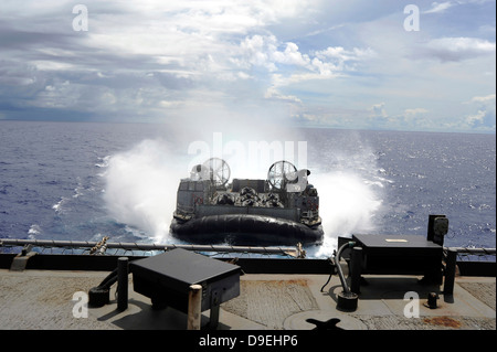 A landing craft air cushion prepares to enter the well-deck of USS Harpers Ferry - Stock Photo