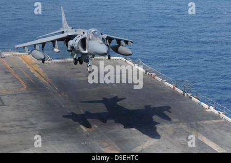 An AV-8B Harrier aircraft lands on the flight deck of USS Peleliu. - Stock Photo