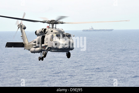 An MH-60R Seahawk helicopter in flight over the Pacific Ocean - Stock Photo