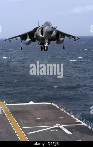 An AV-8B Harrier II prepares to land on the flight deck of USS Nassau. - Stock Photo