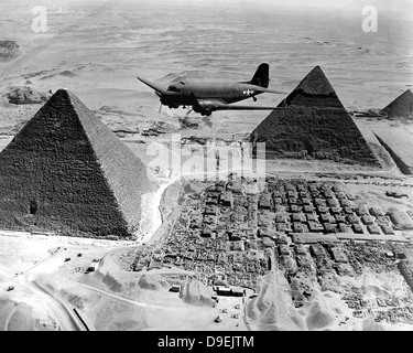 An Air Transport Command plane flies over the pyramids in Egypt. - Stock Photo