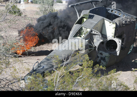 Black smoke rises to the air from a simulated wreckage of a downed UH-1N Huey. - Stock Photo