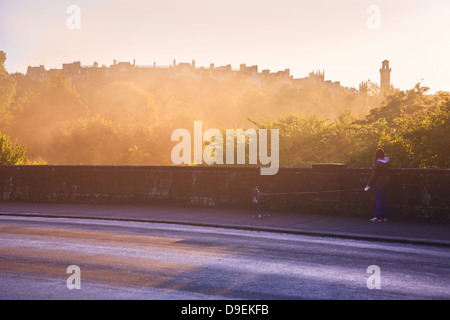 Woman walking her dog on an early winters morning past Kelvingrove Park in Glasgow. - Stock Photo