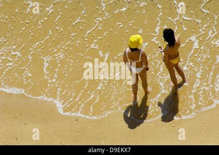 Two solar adorers on a beach Algarve, Portugal. - Stock Photo