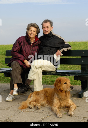 Senior citizen's pair sits on a park-bench, before them lies her dog (Model release) - Stock Photo