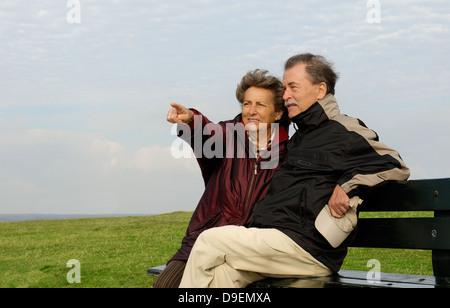 Senior citizen's pair sits on a park-bench (Model release) - Stock Photo