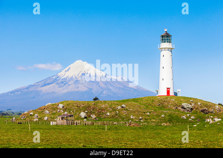 Cape Egmont Lighthouse and Taranaki/Mount Egmont, in the Taranaki Region of New Zealand - Stock Photo