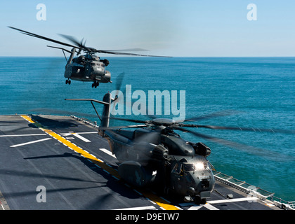 MH-53E Sea Dragon helicopters take off from the flight deck of USS Wasp. - Stock Photo