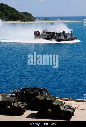 A landing craft air cushion approaches the well deck of USS Denver. - Stock Photo