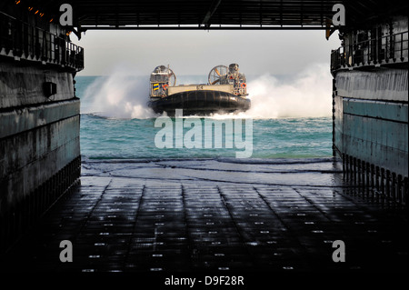 A landing craft air cushion prepares to enter the well deck of USS Pearl Harbor. - Stock Photo