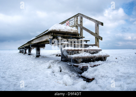 Wooden footbridge on a beach on the Baltic Sea in winter, Boardwalk on a beach At the Baltic Sea in winter - Stock Photo