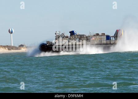 A landing craft air cushion prepares to land on the beach. - Stock Photo