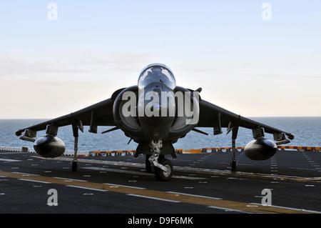 An AV-8B Harrier maneuvers on the flight deck of USS Kearsarge. - Stock Photo
