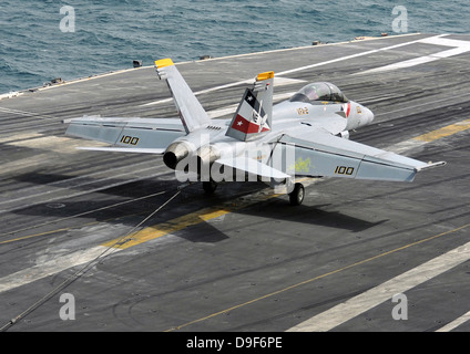 An F/A-18F Super Hornet traps an arresting wire on the flight deck of USS Abraham Lincoln. - Stock Photo