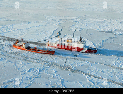 USCG Healy breaks ice around a Russian-flagged tanker south of Nome, Alaska. - Stock Photo