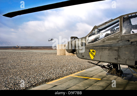 An AH-64D Apache helicopter comes in for a landing at a military base in Afghanistan. - Stock Photo