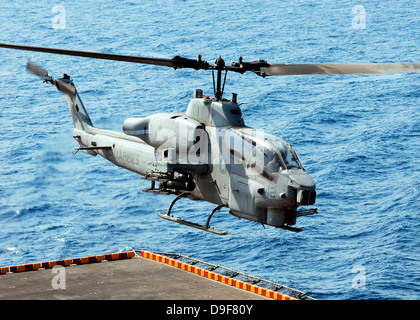 An AH-1W Super Cobra helicopter launches off the flight deck of USS Peleliu. - Stock Photo