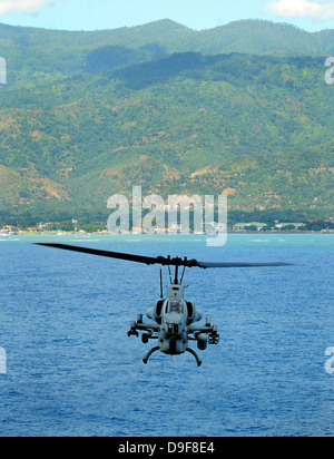 An AH-1W Super Cobra flies off the coast of Dili, East Timor. - Stock Photo