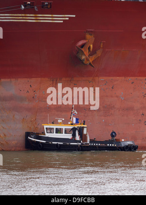 Small boat next to an anchor of the Berge Stahl, one of the largest bulkcarriers in the world. Port of Rotterdam - Stock Photo
