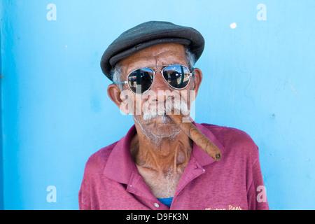 Old man wearing sunglasses and flat cap, smoking big Cuban cigar, Vinales, Pinar Del Rio Province, Cuba, West Indies - Stock Photo