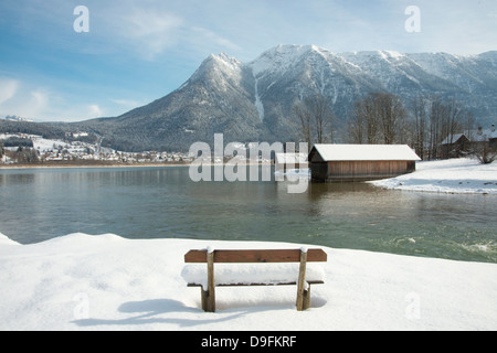 A snow covered bench facing Hallstatter See and the surrounding mountains near the town of Hallstatt, Austria - Stock Photo