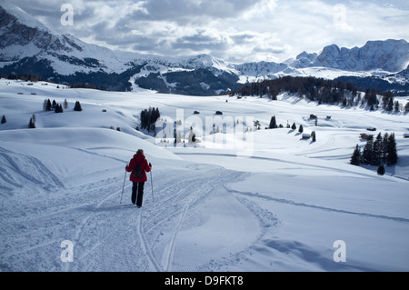 A woman walking on a snowy trail in the Alpe di Siusi Ski resort near the town of Otisei in the Dolomites, South - Stock Photo