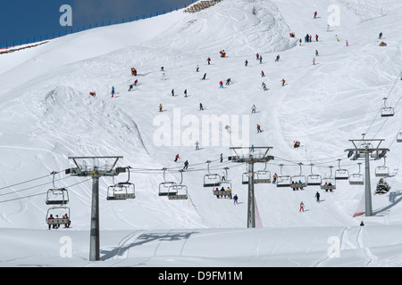 A chairlift and skiers on piste at Passo Sella in the Dolomite Mountains, South Tyrol, Italy - Stock Photo