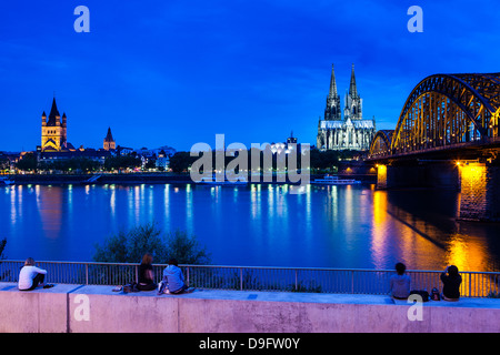 Rhine bridge and Cathedral of Cologne above the River Rhine at night, Cologne, North Rhine-Westphalia, Germany - Stock Photo