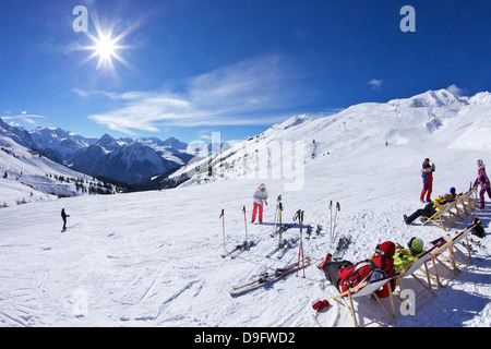 Skiers relaxing at cafe in winter sunshine, Verdons Sud, La Plagne, French Alps, France - Stock Photo