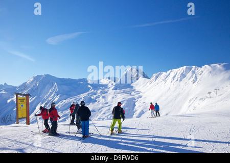Skiers on piste early morning in winter, La Plagne, French Alps, France - Stock Photo