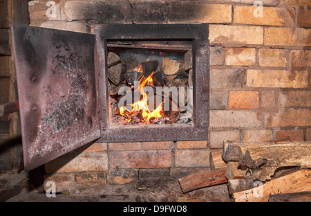 Old stove with open door and burning the wood - Stock Photo