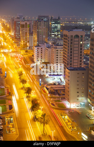 City skyline and Rashid Bin Saeed Al Maktoum Street at dusk, Abu Dhabi, United Arab Emirates, Middle East - Stock Photo