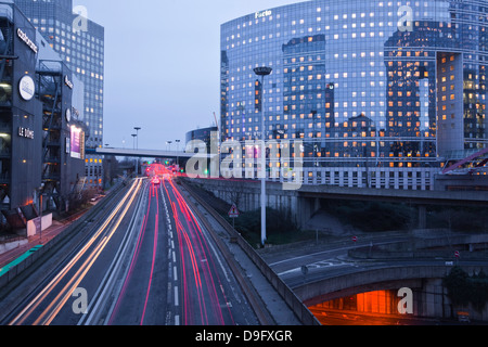 Evening traffic flowing through the La Defense area of Paris, France - Stock Photo