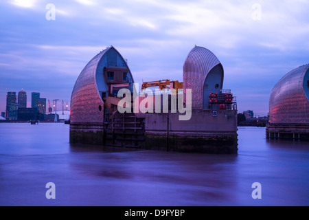 Section of the River Thames Flood Barrier at dusk with Canary Wharf and O2 Arena in the background, London, England, - Stock Photo