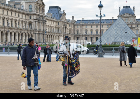 Street traders with goods for sale to tourists outside Musee du Louvre in Paris, France - Jan 2012 - Stock Photo