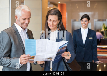 Business couple reading a brochure in front of a hotel reception counter - Stock Photo