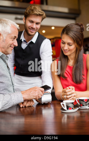 Waiter showing credit card reader to a couple on a table in a restaurant - Stock Photo