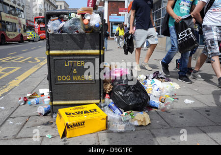 Brighton, UK. 19th June 2013. Shoppers walk past overflowing bins in North Street as rubbish piles up on the streets - Stock Photo