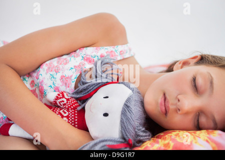 Girl sleeping on the bed with a rag doll - Stock Photo