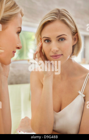Woman checking her face in the mirror - Stock Photo
