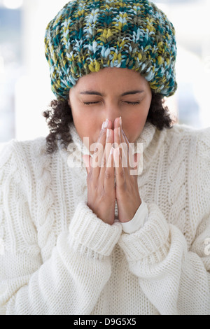 Close-up of a woman blowing her nose - Stock Photo