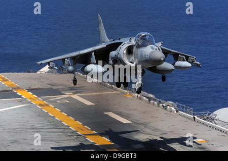An AV-8B Harrier jet lands on the flight deck of USS Essex. - Stock Photo
