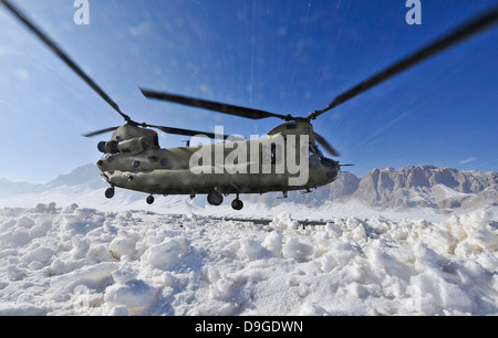 Snow flies up as a U.S. Army CH-47 Chinook helicopter prepares to land - Stock Photo