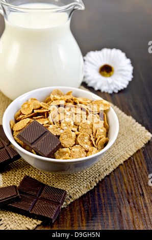 Corn flakes with slices of chocolate, milk in glass jug, hessian cloth, white flower on a wooden board - Stock Photo