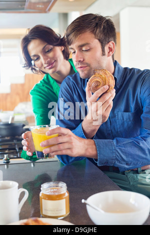 Couple having breakfast at a kitchen counter - Stock Photo