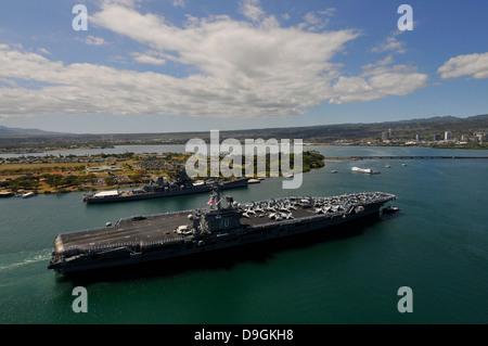 USS Carl Vinson passes the USS Missouri Memorial in Pearl Harbor. - Stock Photo