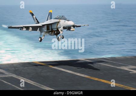 An F/A-18F Super Hornet prepares to land on the flight deck USS Dwight D. Eisenhower. - Stock Photo
