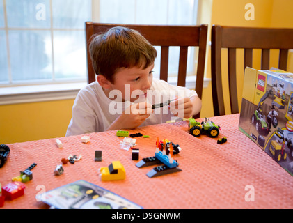 5 Year Old Boy Playing With Lego Bricks In Room Of A House
