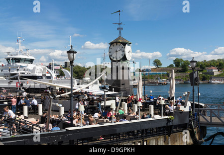 Clock Tower in Pipervika Waterfront, Oslo Harbour, Norway, Europe with people at cafes - Stock Photo